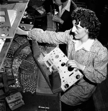 Woman putting mechanical parts on the front panel of a wireless set no. 19