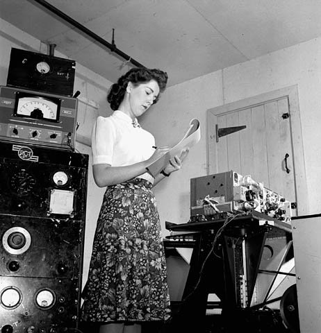 Well dressed woman writes takes notes.  Behind her measuring equipment, in front of her a complete wireless set no. 19.
